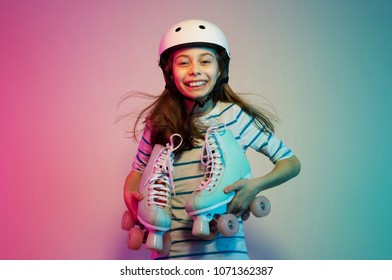 Happy smiling young caucasian child girl in safety helmet holding pastel roller skates - hobby, sports and active lifestyle concept. Colorful background, layout with free text (copy) space.