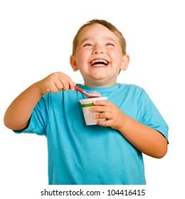 Happy smiling young child eating yogurt isolated on white