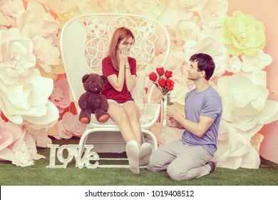 Happy smiling young couple looking at each other, handsome young man giving beautiful girl a bouquet of red roses, Girl holding a lovely bear in her arm. Love, valentine's day concept.
