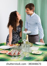 Happy smiling young couple serving table for festive dinner at home