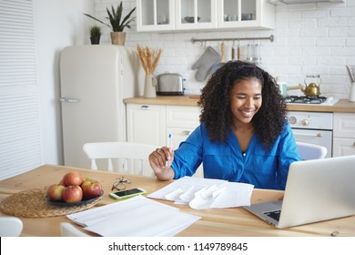 Happy smiling young dark skinned female sitting at dining table in front of open laptop, using wifi, paying domestic bills online, working through finances, happy to realize that savings grow