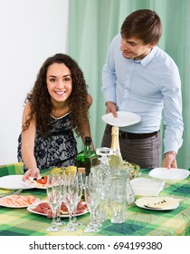Happy smiling young family preparing for guests visit at home