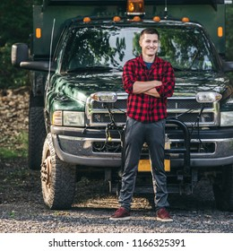 Happy smiling young farmer man standing in front of pickup truck readty to work