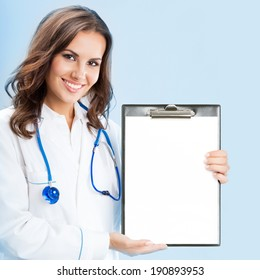 Happy smiling young female doctor showing okay gesture, over blue background