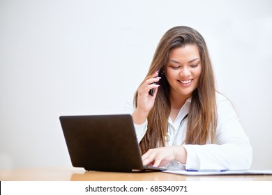 Happy smiling young female hispanic doctor sitting behind the desk, typing into a laptop, talking on the mobile phone and looking into a paper documents on her table