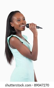 Happy smiling young female singer against a white background
