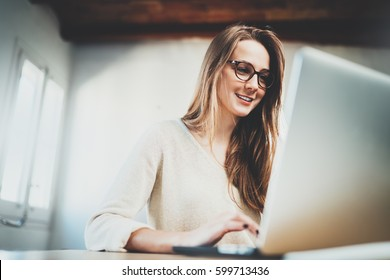 Happy smiling young female student using laptop at library, cheerful hipster girl working on portable computer at vintage loft, attractive businesswoman working via computer at modern office