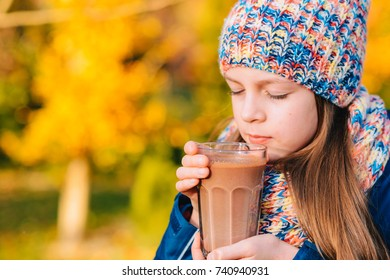 Happy smiling young girl drinking chocolate milk