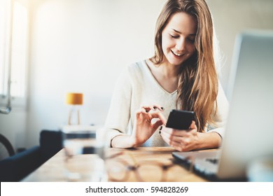 Happy smiling young girl send an sms message to her best friend while working at modern office, cheerful woman using smartphone at home interior, joyful hipster girl chatting via cellphone