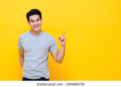 Happy smiling young handnsome Asian man pointing hand up to copy space aside