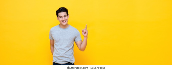 Happy smiling young handnsome Asian man pointing hand up to copy space aside on yellow banner background