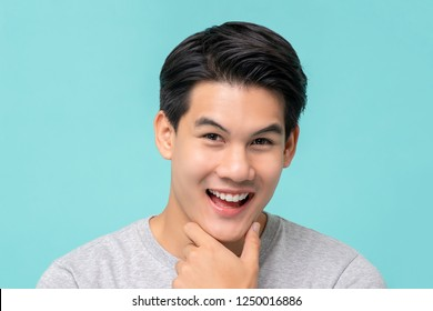 Happy smiling young handsome Asian man face with hand touching chin studio shot isolated on light blue background