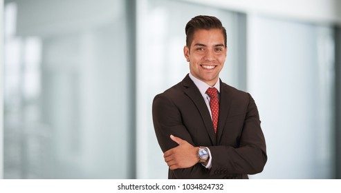 Happy smiling young Hispanic businessman standing in office with arms crossed looking at camera