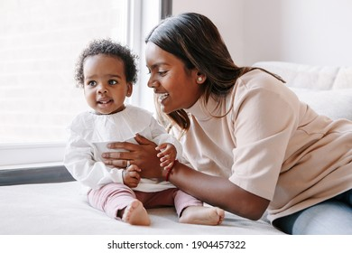 Happy smiling young Indian mother playing with black baby girl daughter. Family mixed race people mom and kid together hugging at home. Authentic candid lifestyle with infant kid child.