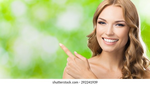 Happy smiling young lovely blond woman showing blank copyspace area for slogan or text message, outdoors