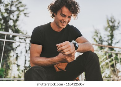 Happy smiling young male wears black t-shirt and wears wirstwatch on the street. Cheerful man posing for advertisement with copy space, outdoor in the city street. People concept