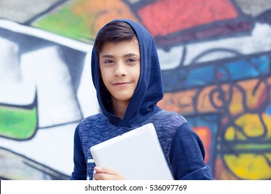 Happy smiling young man, boy looking at you camera holding tablet pad present touch screen with copy space, isolated graffiti wall background. Positive face expressions, emotions. Back to school gift