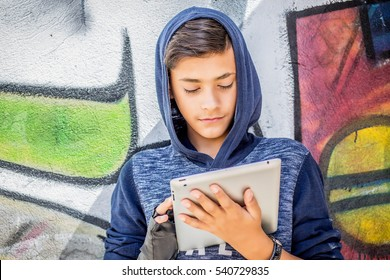 Happy smiling young man, boy holding looking at tablet pad computer present,  touch screen with copy space, isolated graffiti wall background. Positive face expressions, emotions. Back to school gift