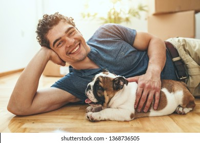 A happy smiling young man is lying down on a floor in the living room of his new apartment and holding a little puppy.