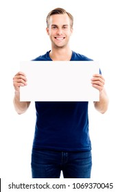Happy smiling young man showing blank signboard with empty copyspace area for slogan or advertising text message, isolated on white background. Caucasian male model in advertisiment concept.