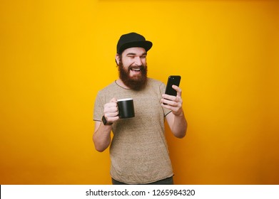 Happy smiling young man is texting on mobile, and holding a cup of tea or coffee