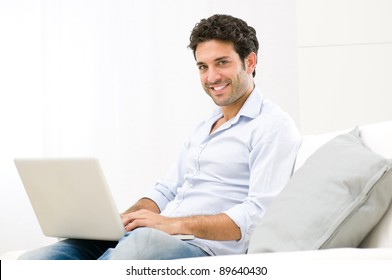 Happy smiling young man working on laptop computer at home