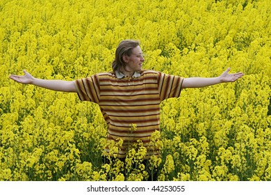 Happy and smiling young man in the yellow flower meadow.