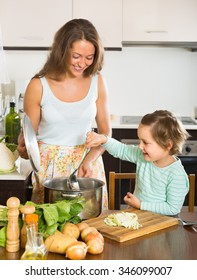 Happy smiling young mother with little girl cooking at home kitchen