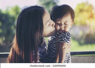 Happy smiling young mother with little baby, childhood, care, child and parenthood concept.
