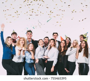 Happy smiling young people with gift boxes and blowing party whistles. Celebration concept.