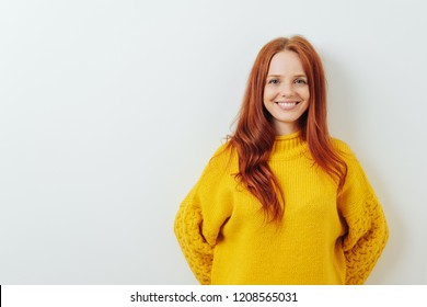 Happy smiling young redhead woman posing in a colorful yellow top against a white wall with copy space