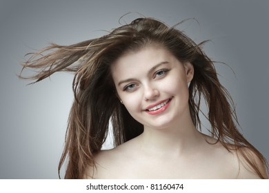 Happy smiling young sexy woman with hair flowing under wind