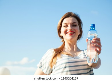 Happy smiling young woman with a bottle of drinking water outside