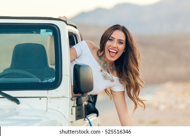 Happy Smiling Young Woman In Convertible Car Hanging Out Window With Hair In Wind.