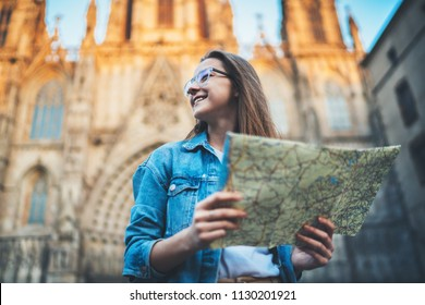 Happy smiling young woman exploring historical landmarks of Barcelona, happy traveller woman enjoying in the old Gothic Quarter in Barcelona, female tourist planning route on map, Summer Vacation
