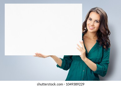 Happy smiling young woman in green confident clothing showing blank signboard with copyspace empty area for some text or slogan, over grey background. Success in business and advertising concept.