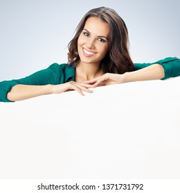 Happy smiling young woman in green confident clothing showing blank signboard with copyspace empty area for some text or slogan, over grey background. Success in business and advertising concept photo