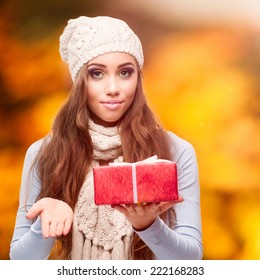 happy smiling young woman holding gift over autumn background
