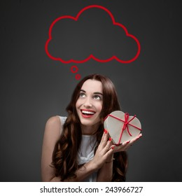 Happy and smiling young woman holding heart box with candies on grey background. Happy valentines gift concept
