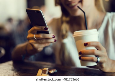 Happy smiling young woman makes on-line shopping with internet on mobile phone application, female tourist browsing in coffee shop, attractive girl hold smart phone while laughing and looking to you