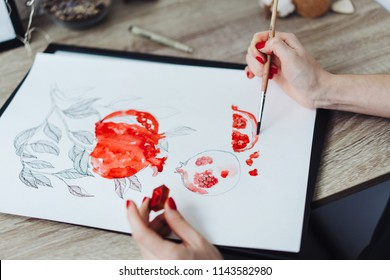Happy smiling young woman painting with watercolor paints
