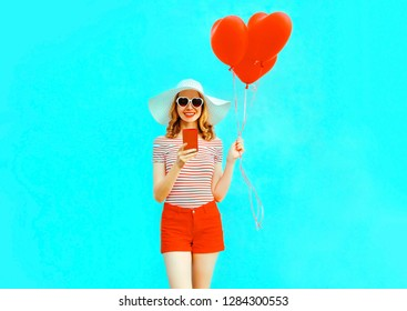 Happy smiling young woman with phone, red heart shaped air balloons in summer straw hat and shorts on colorful blue background