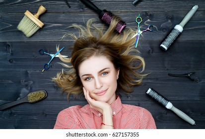 Happy smiling young woman in plaid shirt with hand on her chin and hairdresser tools among her. Top view