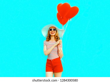 Happy smiling young woman with red heart shaped air balloons in summer straw hat and shorts on colorful blue background
