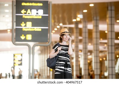 Happy smiling young woman in straw summer hat waiting for flight in modern airport terminal building, holding mobile phone, making call