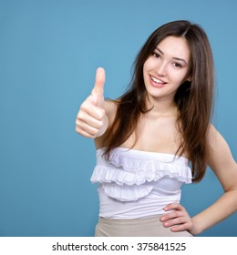 Happy smiling young woman with thumbs up gesture, isolated on blue background