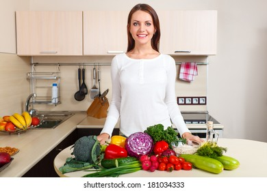 happy smiling young woman with vegetables at kitchen