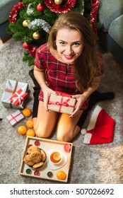 Happy smiling young woman wearing red dress and long stockings, sitting on the floor near Christmas tree, mandarins and cookies and enjoying her gifts. Christmas and New Year holidays