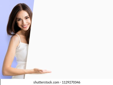 Happy smiling young woman in white casual smart clothing, showing empty blank signboard with copyspace area for text or slogan, over violet background