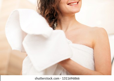 Happy smiling young woman wiping her hair with a towel after a shower